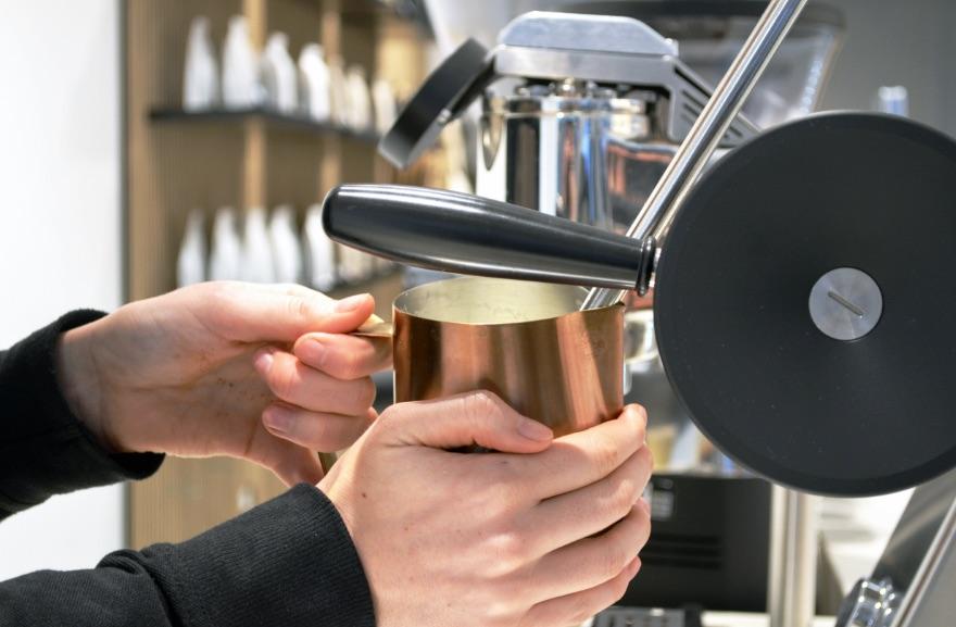 Koffiebar Amsterdam, Barista die een koffie schenkt met een koffieapparaat van de koffiezaak Cafecito